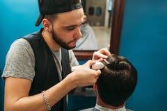 Młodego fryzjera męskiego mężczyzna rżniętego włosy bezpłatna przestrzeń Obrazy Stock
