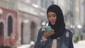Młodego muzułmańskiego kobiety dosłania głosu audio wiadomość na telefonie komórkowym przy plenerowy opowiadać mobilny asystent D zdjęcie wideo