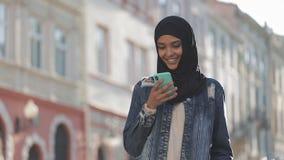 Młodego muzułmańskiego kobiety dosłania głosu audio wiadomość na telefonie komórkowym przy plenerowy opowiadać mobilny asystent D zbiory