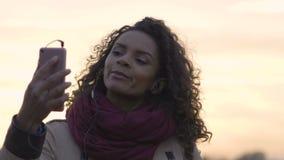 Młodego pięknego kobiety dopatrywania ulubiona muzyczna klamerka na smartphone, tanczy zbiory
