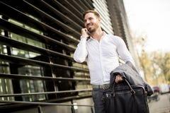Młodego pomyślnego mężczyzna wykonawczy biznesmen używa jego wiszącą ozdobę cel fotografia royalty free