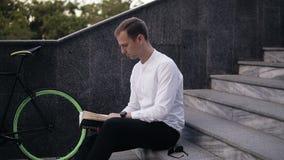 Młodego poważnego caucasian mężczyzna czytelnicza książka, siedzi na miasto miastowych schodkach, studiowaniu lub czytaniu, wolny zbiory
