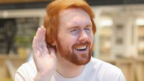 Młodego przypadkowego rudzielec brody mężczyzna słuchający sekret, informacja zdjęcie wideo