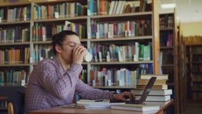 Młodego przystojnego modnisia męski uczeń siedzi przy stołem w lighty dużej bibliotece z laptopem przed on, drukujący i zbiory wideo