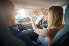 Młodego rodzinnego kupienia pierwszy elektryczny samochód w sali wystawowej Atrakcyjna kobieta patrzeje w lustro w kabinie nowoży zdjęcie stock