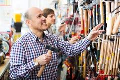 Młodego sprzedawcy pomaga klient wybierać młot Zdjęcie Stock