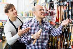 Młodego sprzedawcy pomaga klient wybierać młot Zdjęcia Stock