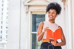 Młodego Szczęśliwego amerykanin afrykańskiego pochodzenia żeński student collegu z afro fryzury obsiadaniem rocznika stylu budynk obrazy stock