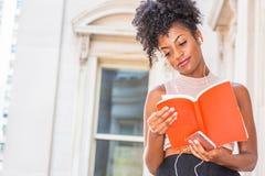 Młodego Szczęśliwego amerykanin afrykańskiego pochodzenia żeński student collegu z afro fryzury obsiadaniem rocznika stylu budynk fotografia royalty free