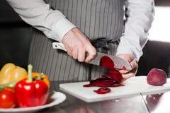 Młodego szefa kuchni tnący burak na białej tnącej desce Zbliżenie ręka z nożowym tnącym świeżym warzywem Gotować w a Zdjęcia Stock