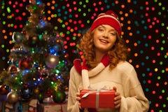 Młodego uśmiechniętego kobiety mienia czerwony bożych narodzeń prezent Obraz Royalty Free