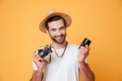 Młodego uśmiechniętego mężczyzna przyglądająca kamera podczas gdy trzymający obiektyw Obraz Stock