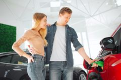 Młodego uśmiechniętego rodzinnego kupienia pierwszy elektryczny samochód w sali wystawowej Obsługuje ładuje nowożytnego życzliweg fotografia stock