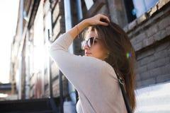 Młodej ładnej kobiety mody plenerowy portret Pięknej dziewczyny przypadkowa suknia i okulary przeciwsłoneczni obraz stock