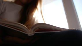 Młodej ślicznej blondynki dziewczyny nastoletni obsiadanie na windowsill, studiowaniu i czytaniu, podręcznik zbiory