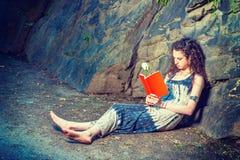 Młodej Amerykańskiej kobiety czerwieni czytelnicza książka, siedzi na ziemi, podróż Obrazy Royalty Free