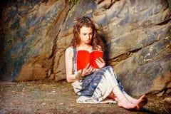 Młodej Amerykańskiej kobiety czerwieni czytelnicza książka, siedzi na ziemi, podróż Zdjęcia Stock