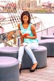 Młodej amerykanin afrykańskiego pochodzenia kobiety czytelnicza książka, relaksuje rzeką wewnątrz Obrazy Stock