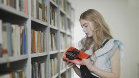 Młodej atrakcyjnej blondynki studencka dziewczyna bierze dwa książki od półki w bibliotece