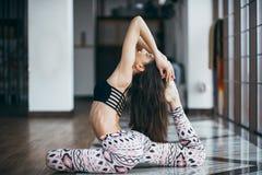Młodej atrakcyjnej kobiety ćwiczy joga blisko okno Obraz Royalty Free