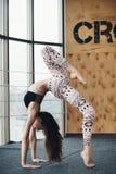 Młodej atrakcyjnej kobiety ćwiczy joga blisko okno Zdjęcia Royalty Free