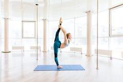 Młodej atrakcyjnej kobiety ćwiczy joga jest ubranym sportswear, zieleni spodnia, popielaty stanik, salowa pełna długość Obrazy Royalty Free