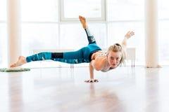 Młodej atrakcyjnej kobiety ćwiczy joga jest ubranym sportswear, zieleni spodnia, popielaty stanik, salowa pełna długość Zdjęcia Stock