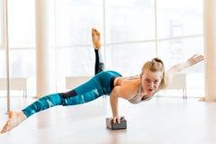 Młodej atrakcyjnej kobiety ćwiczy joga jest ubranym sportswear, zieleni spodnia, popielaty stanik, salowa pełna długość Zdjęcie Royalty Free