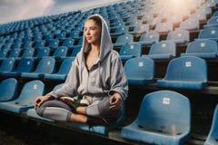 Młodej atrakcyjnej kobiety ćwiczy joga, siedzi w Padmasana ćwiczeniu, Lotosowa poza na medytaci sesi, pracujący out jest ubranym  Obrazy Stock