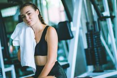 Młodej atrakcyjnej kobiety caucasian obsiadanie i używać wycierać pot ręcznik Relaks po ciężkiego treningu w gym fotografia stock