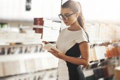Młodej atrakcyjnej kobiety czytelnicza książka w książkowym sklepie obok książkowej półki obraz stock