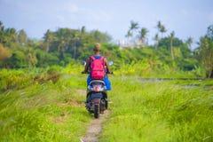 Młodej atrakcyjnej turystycznej afro Amerykańskiej murzynki jeździecki motocykl szczęśliwy w pięknej Azja wsi wzdłuż zielonych ry Fotografia Royalty Free