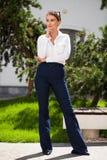 Młodej blondynki biznesowa kobieta w niebieskich dżinsach i białej koszula obraz royalty free