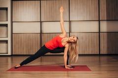 Młodej blondynki kobiety ćwiczy joga, - Virabhadrasana Wirował wojownik pozę obraz royalty free