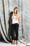 Młodej blondynki piękna dziewczyna siedzi na szpilkach zdjęcia royalty free