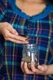 Młodej brunetki kobiety okładzinowa kamera, mienie szklany słój wypełnia je z monetami Zdjęcie Royalty Free