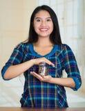 Młodej brunetki kobiety okładzinowa kamera, mienie szklany słój z monetami inside, ono uśmiecha się szczęśliwie Fotografia Stock