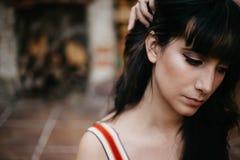 Młodej brunetki smutna i melancholijna dziewczyna z czarni włosy ciągnięcia włosy zdala od jej twarzy fotografia royalty free