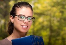 Młodej brunetki wzorcowi jest ubranym szkła pozuje trzymający książkę, intelektualny pojęcie Zdjęcia Royalty Free