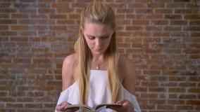 Młodej caucasian blondynki dziewczyny czytelnicza książka, portret, ściana z cegieł w tle