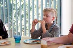 Młodej chłopiec przyglądający zmęczony przy kuchennego stołu łasowania grzanką dla śniadania fotografia royalty free
