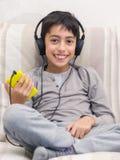 Młodej chłopiec słuchający muzyczny hełmofon Zdjęcia Royalty Free