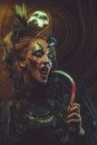 Młodej czarownicy hloding sierp Jaskrawy uzupełniał, czaszka, dymu Halloween temat Zdjęcia Royalty Free