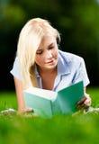 Młodej damy lying on the beach na trawie i czytelniczej książce obrazy stock