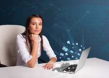 Młodej damy obsiadanie przy dest i pisać na maszynie na laptopie z wiadomości ico Obraz Royalty Free