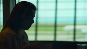 Młodej damy obsiadanie w lotniskowej restauraci i cieszyć się gorącą kawę, turystyka zbiory