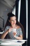 Młodej damy pić kawowy przez okno i patrzeć podczas gdy siedzący w kawiarni Obraz Stock