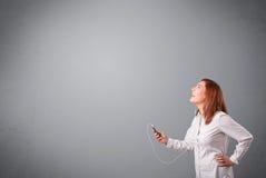 Młodej damy słuchanie muzyka z kopii przestrzenią i śpiew Obrazy Stock