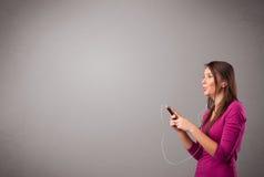 Młodej damy słuchanie muzyka z kopii przestrzenią i śpiew Fotografia Stock