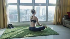 Młodej dziewczyny ćwiczy joga z pejzażu miejskiego tłem w domu zbiory wideo